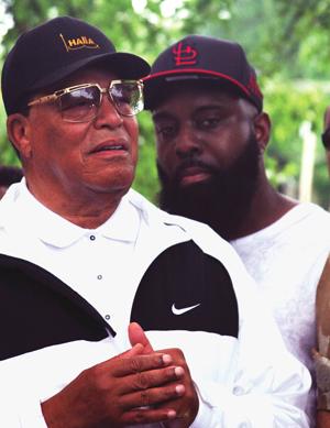 Minister Farrakhan speaks at a memorial for Michael Brown Jr. in Ferguson, Mo. as Michael Brown Sr. looks on. Photo: Final Call