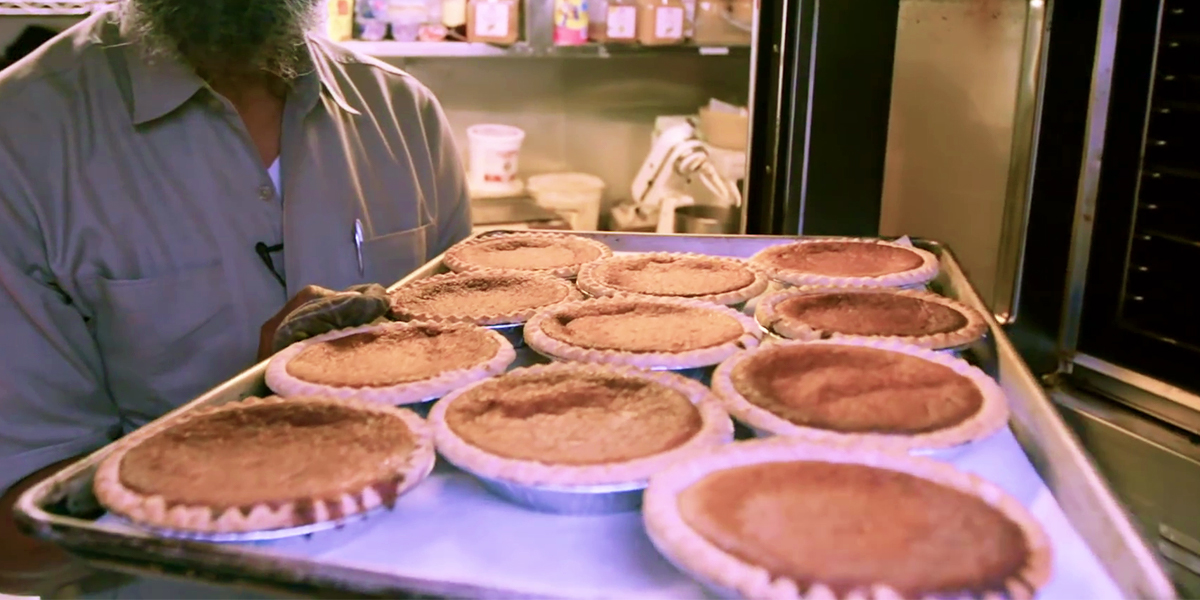 A baker presents a tray of bean pies